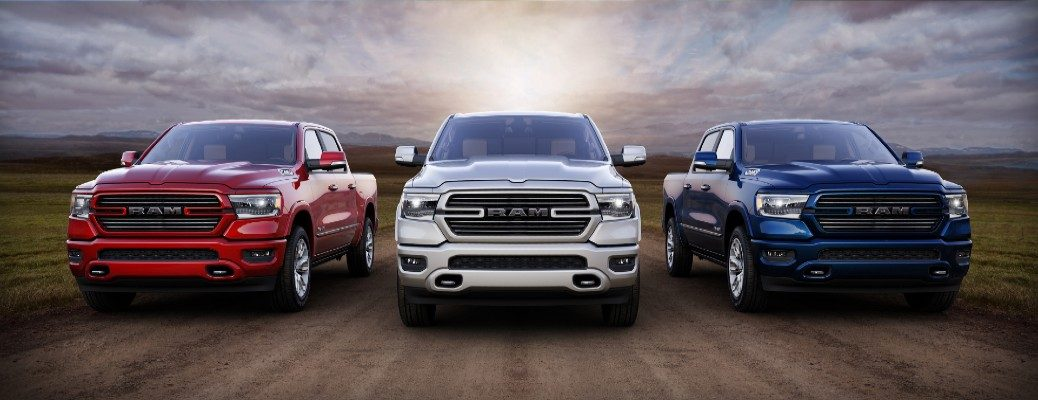 2020 Ram 1500 Laramie Southwest Edition models exterior shot in red, white, and blue driving down a dirt road