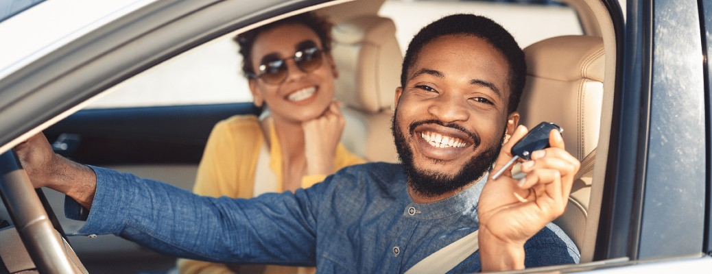 a happy and smiling couple sitting inside a vehicle at a car dealership and holding up the key fob