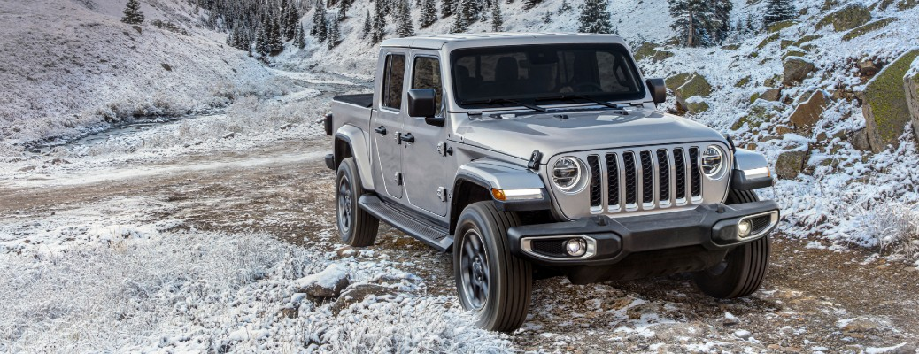 2020 Jeep Gladiator North Edition exterior shot with silver paint color parked on a rode in a snowy mountain forest wilderness