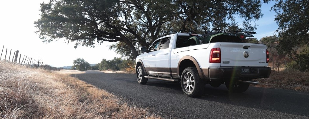 2020 Ram 2500 Laramie Longhorn exterior rear shot with white paint color parked on a back woods country road