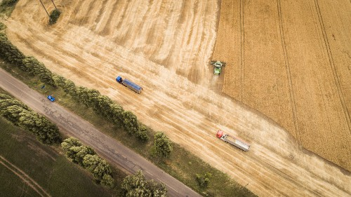 aerial overhead view of combine unloading grain from a farm field