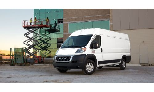 2020 Ram ProMaster exterior shot with white paint color parked outside a building with construction workers on a lift
