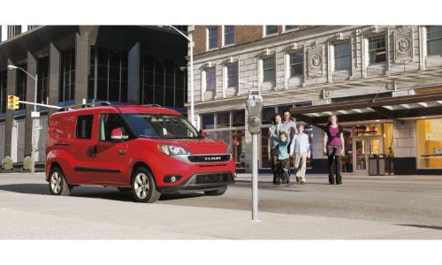 2020 Ram ProMaster City exterior shot with red paint color parked on the side of a street as a family passes