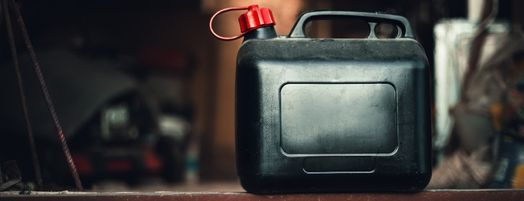 a black plastic fuel can resting on brick in a garage