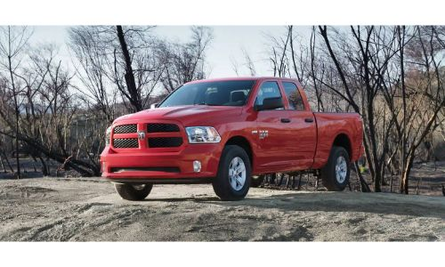 2020 Ram 1500 Classic pickup truck exterior shot with red paint color parked on a sand hill near bare trees