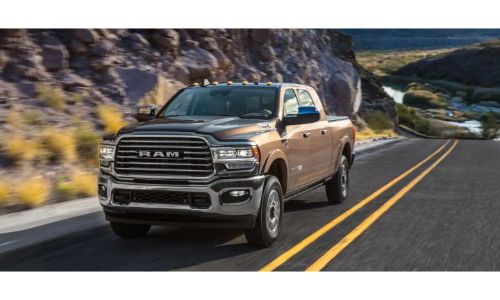 2020 Ram 2500 pickup truck exterior shot with bronze paint color driving on a mountain highway