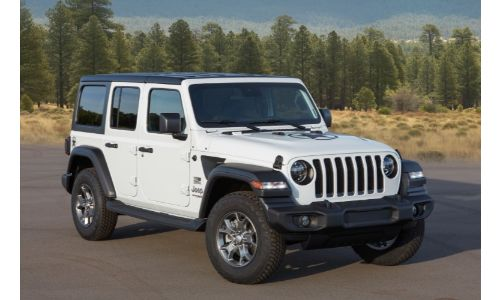 2021 Jeep Wrangler Freedom Edition with white clear coat paint color parked on an empty lot near a forest of pine trees