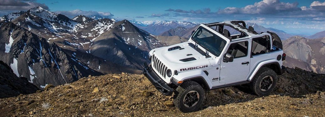 A Jeep Wrangler parked on a hill with mountains in the background