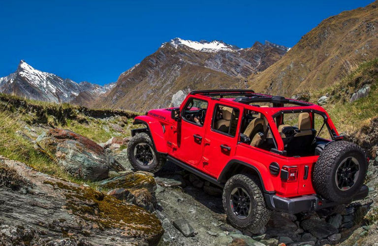Jeep Wrangler driving up a rocky hill