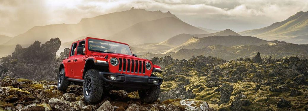 A Jeep Wrangler parked on some rocks