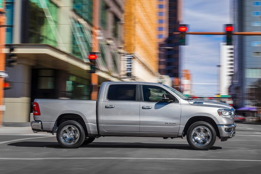 Passenger angle of a white 2019 RAM 1500 driving through a city intersection
