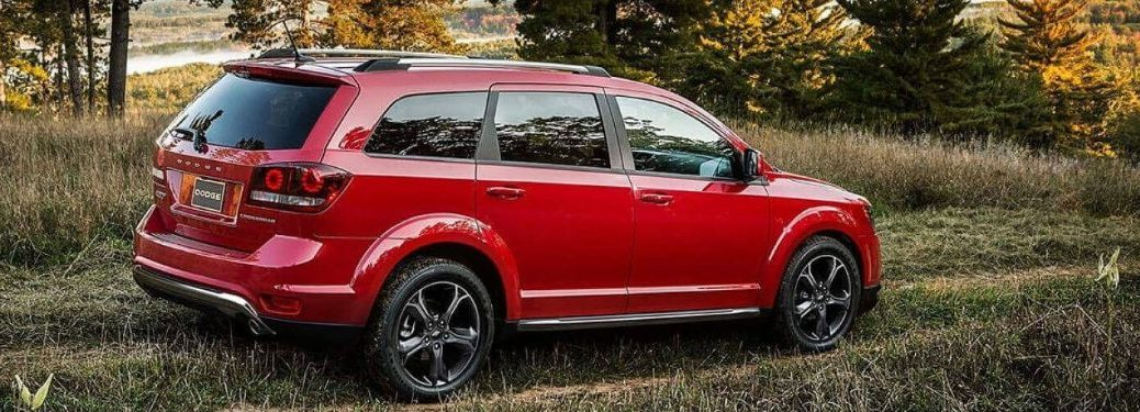 Rear passenger angle of a red 2019 Dodge Journey parked in grass