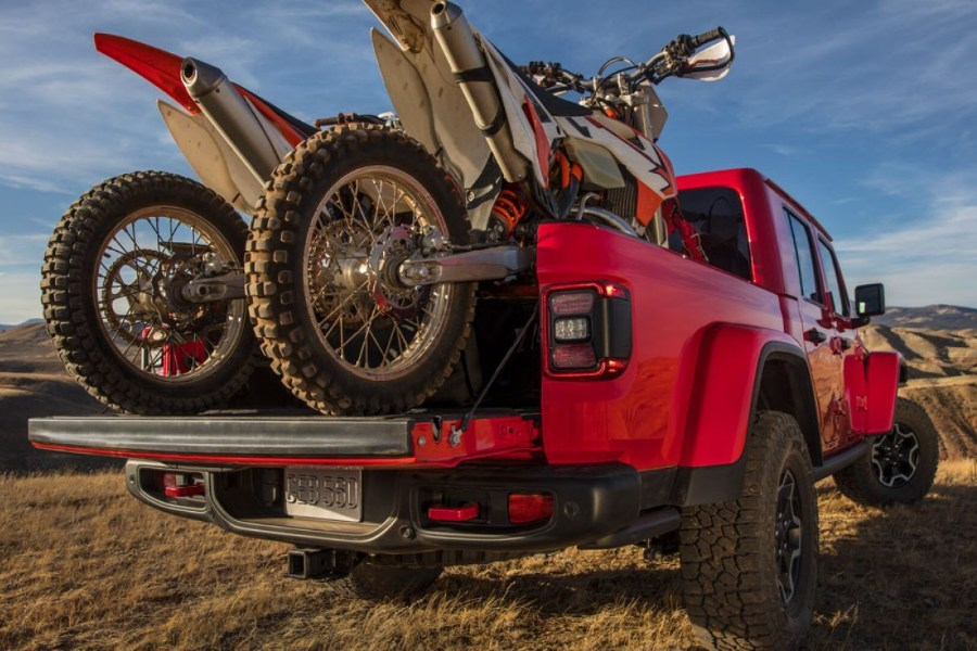 Rear passenger angle of a red 2020 Jeep Gladiator with motor bikes loaded in the back