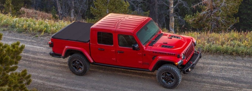 Front passenger aerial angle of a red 2020 Jeep Gladiator with its bed covered driving down a dirt road