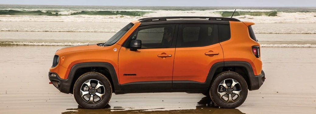 Driver angle of an orange 2019 Jeep Renegade parked on a beach next to the ocean