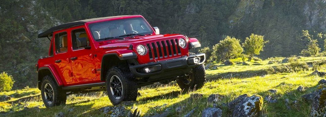 Front passenger angle of a red 2019 Jeep Wrangler parked in a grassy field