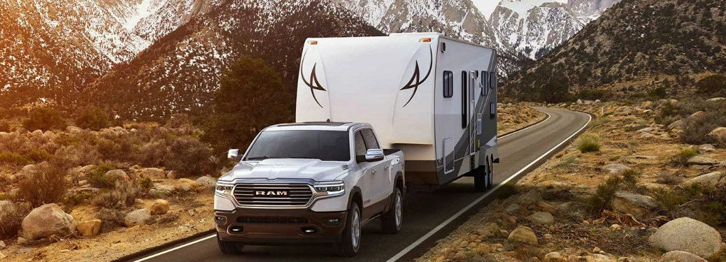 2019 Ram 1500 towing a camper on a road