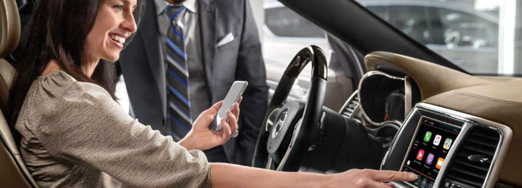 Woman connecting a phone to her car