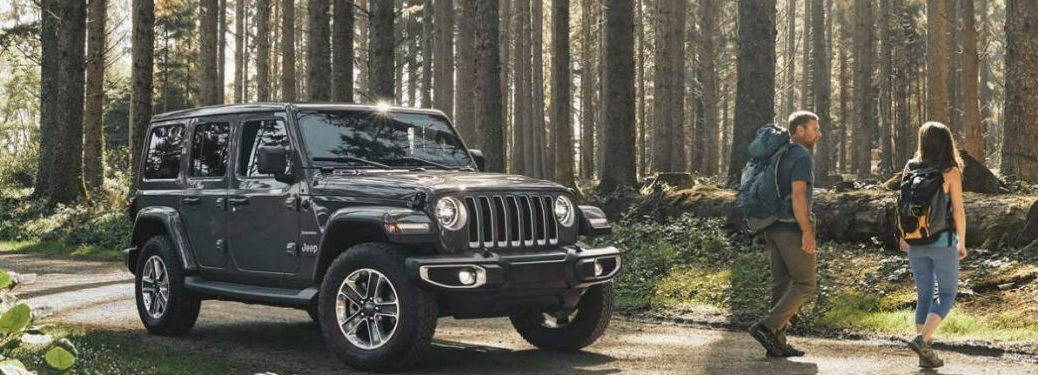 2020 Jeep Wrangler parked with two people standing in front of it