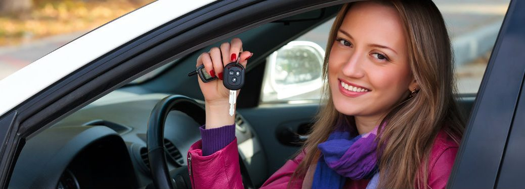 A woman sitting in a car holding a key