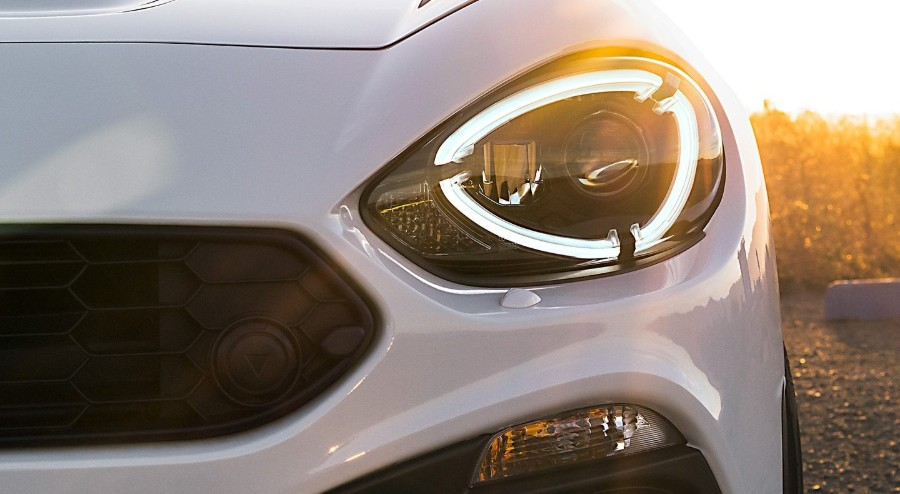 Close up of the front driver headlight and grille on a white 2019 FIAT 124 Spider
