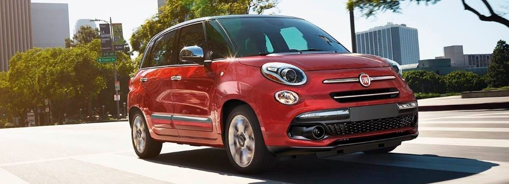 Front passenger angle of a red 2019 FIAT 500L driving on an empty road in the city