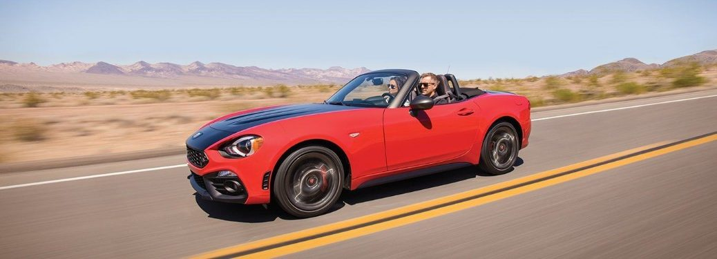Front driver angle of a couple driving in a red 2019 FIAT 124 Spider with the top down