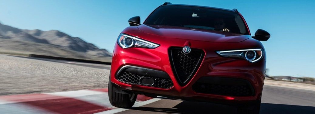 Front angle of a red 2019 Alfa Romeo Stelvio driving on a race track