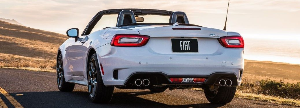Rear driver angle of a white 2019 FIAT 124 Spider driving down a road with its top put down