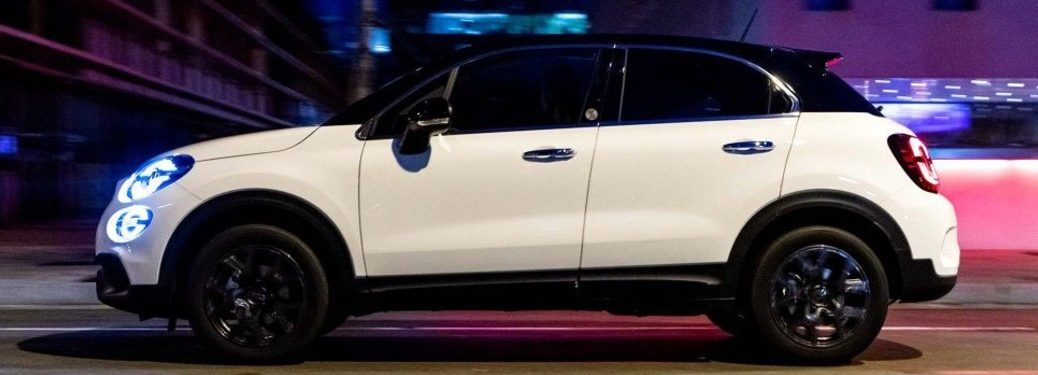 Driver angle of a white 2019 FIAT 500X 120th Anniversary Edition driving in a city at night