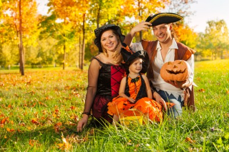 Happy family sitting in the grass while dressed in Halloween costumes