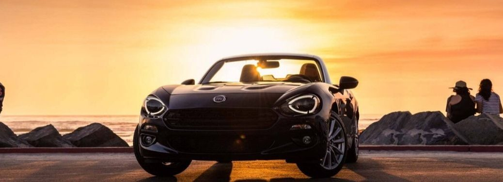 Black 2020 Fiat 124 Spider from front exterior with sunset and ocean behind