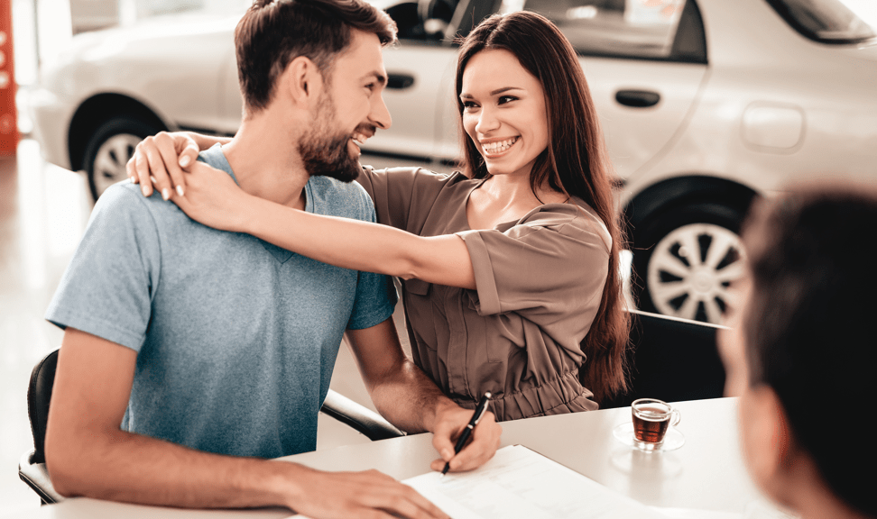 Happy couple purchasing a car