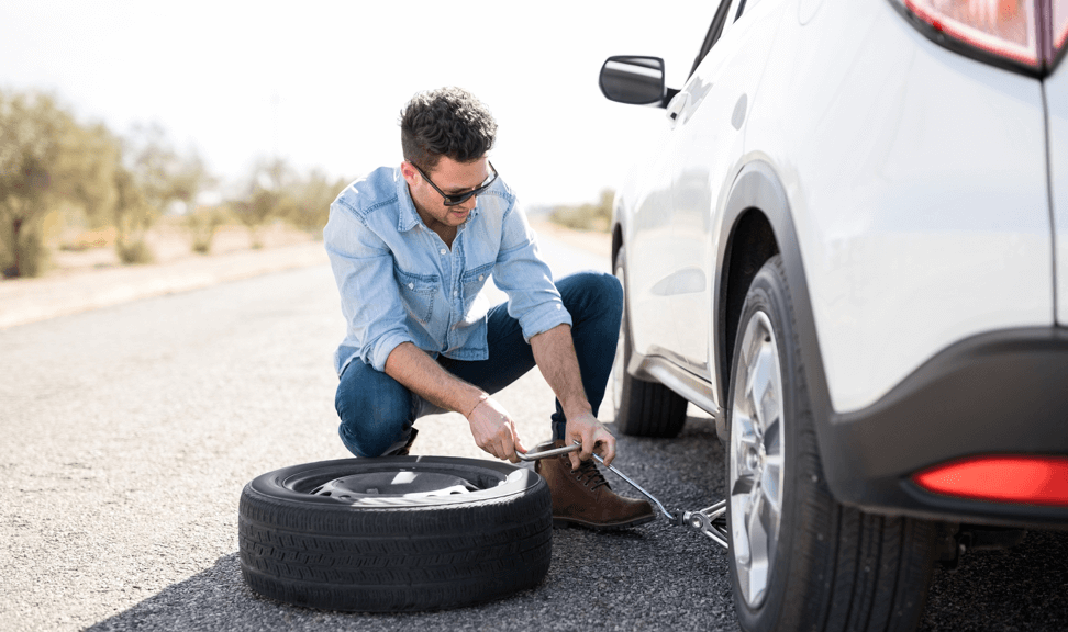 man changing a car tire on side of the road