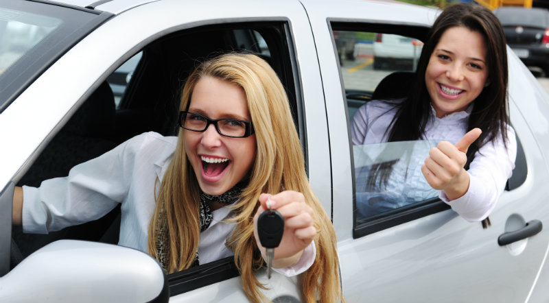 Two women happy in a car after getting a car loan