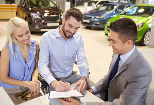 husband and wife working out a loan on a new car