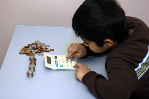 boy counting his coins with the help of a calculator