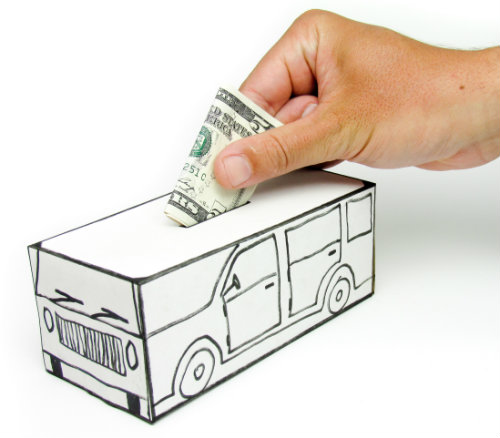 hand putting $5 into a bank shaped liked a car