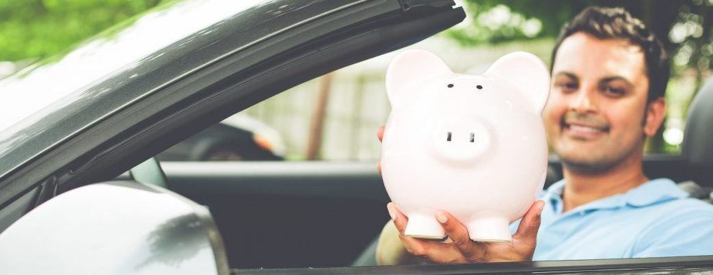 Closeup portrait young man in blue polo shirt showing pink piggy bank inside new sports car isolated outdoors background. Happy to have good low apr interest rates finance rebate deals