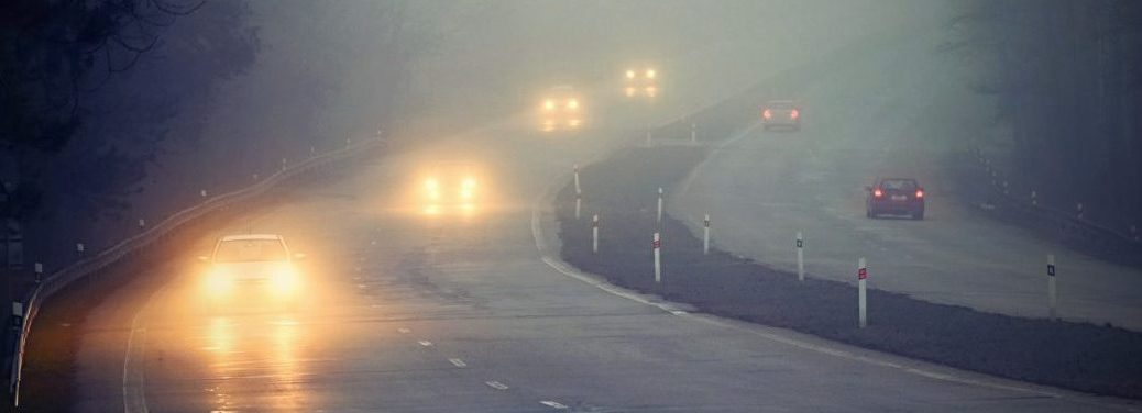 cars driving in the fog on a curvy road with their headlights on