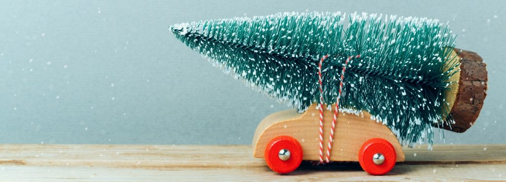 wooden toy car with a pine tree figurine tied to the top with string while fake snow falls