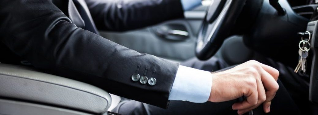 man wearing a suit driving a vehicle