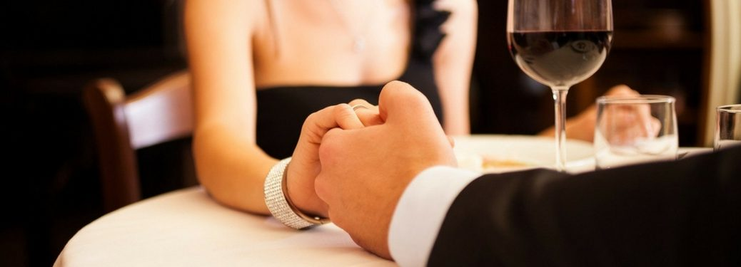 couple holding hands at table at a restaurant