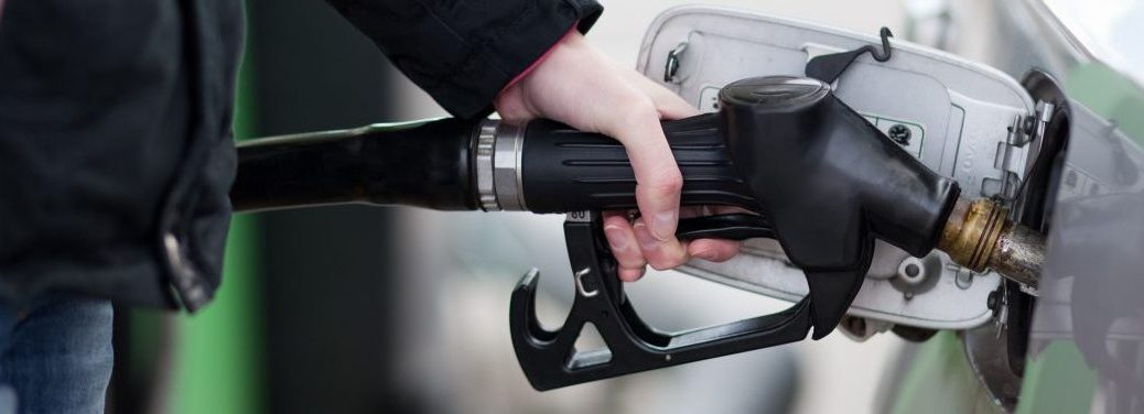 hand holding fuel pump to a car at a gas station