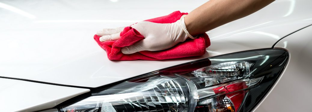 person cleaning exterior of white car with red cloth