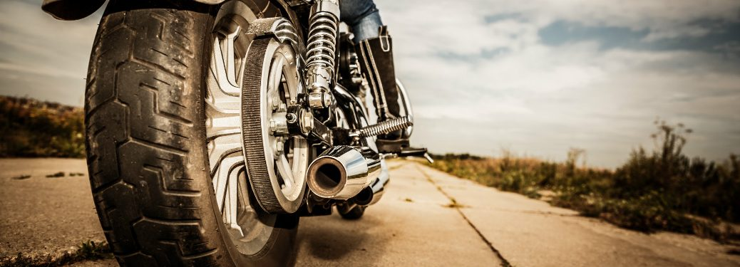 close up of rear wheel and body of motorcycle with person riding on empty desert road