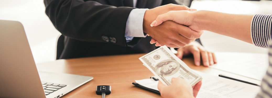 woman shaking hand of salesman while holding money in other hand