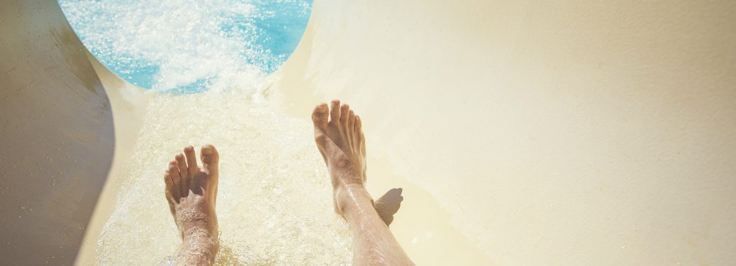 POV view of man sliding down waterslide into pool