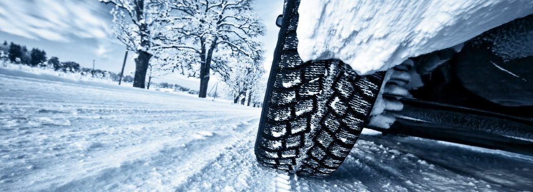 close up of car tire driving on snowy road