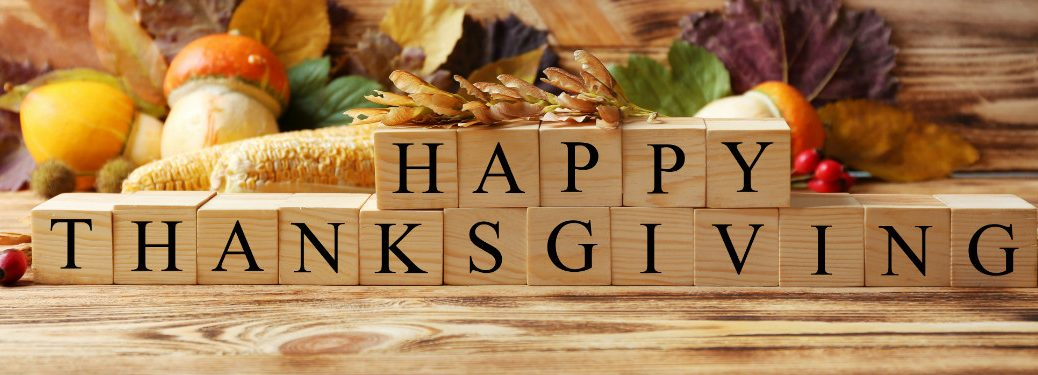 happy thanksgiving spelled out on wooden blocks surrounded by fall decorations